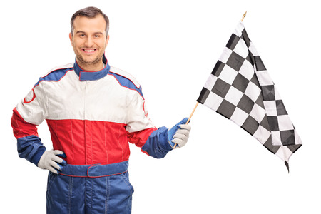 racer flag: Young man in a racing suit waving a checkered race flag and looking at the camera isolated on white background