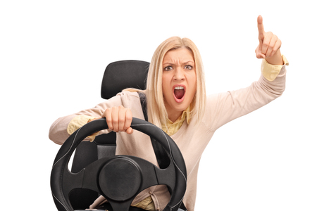 provoked: Angry woman pretending to drive and shouting towards the camera isolated on white background