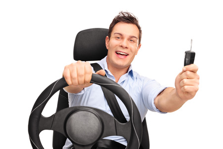keys isolated: Young man sitting on a car seat fastened with seatbelt and holding a car key isolated on white background