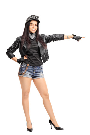 biker girl: Full length portrait of a female biker in a black leather jacket pointing with her hand to the right isolated on white background Stock Photo
