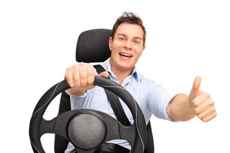 うれしそうな若い男が運転と、白い背景で隔離を親指をあきらめる