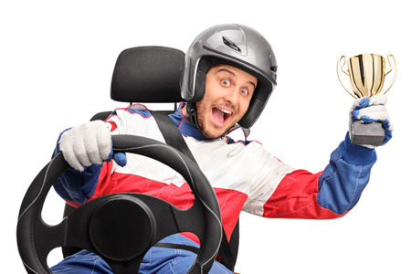 race car driver: Excited car racer holding a gold trophy seated on a car seat and looking at the camera isolated on white background
