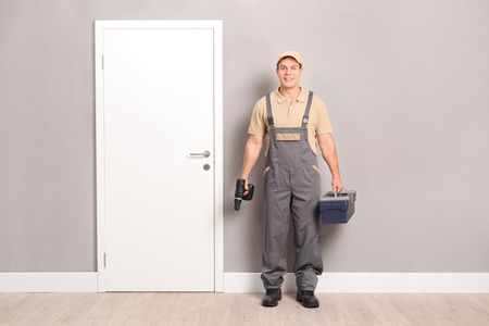 locksmith: Young male locksmith holding a drill and a toolbox and standing next to a door indoors Stock Photo