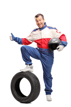 posing  agree: Full length portrait of an excited car racer holding a helmet and giving a thumb up isolated on white background Stock Photo