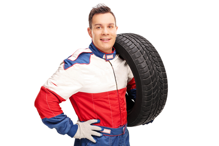 shoulder carrying: Young male car racer carrying a tire on his shoulder and looking at the camera isolated on white background