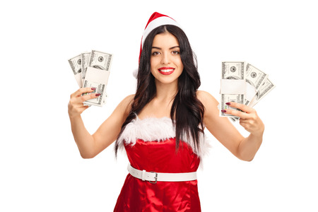 woman holding money: Young woman in Santa costume holding few stacks of money and looking at the camera isolated on white background