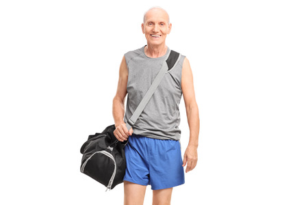 Active senior man in sportswear carrying a sports bag and walking isolated on white background