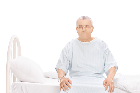 recovering: Senior patient in a hospital gown sitting on a bed and looking at the camera isolated on white background