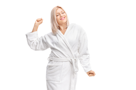 bath robes: Young woman in a white bathrobe stretching herself isolated on white background Stock Photo
