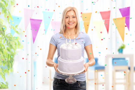 Cheerful young woman holding a birthday cake and looking at the camera at homed