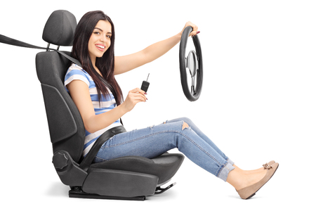 single: Young woman holding a car key and a steering wheel seated on a car seat isolated on white background