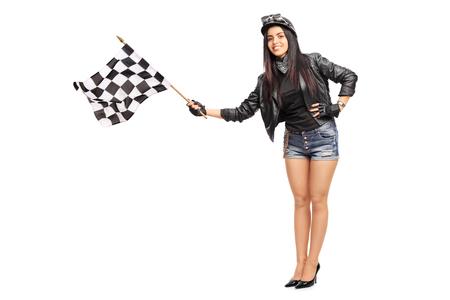 Ritratto integrale di un giovane motociclista femminile sventolando una bandiera a scacchi gara isolato su sfondo bianco