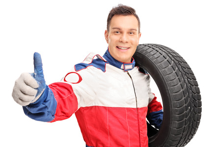 llantas: Joven piloto de coches masculina de un neumático y que da un pulgar hacia arriba aislados en fondo blanco