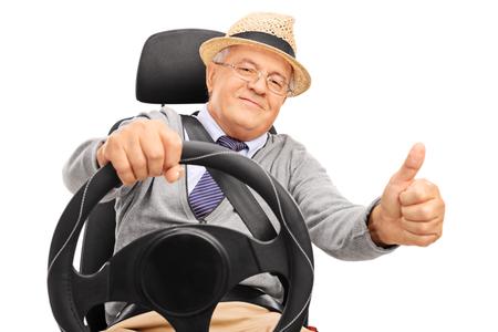 ancianos felices: Hombre mayor pretendiendo conducir y dando un pulgar hacia arriba aislados en fondo blanco