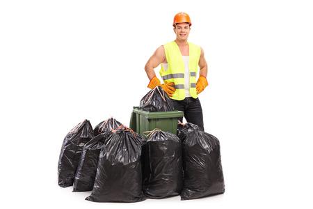 basura: Colector de residuos joven en el chaleco reflectante verde que presenta detrás de un par de bolsas de basura aisladas sobre fondo blanco