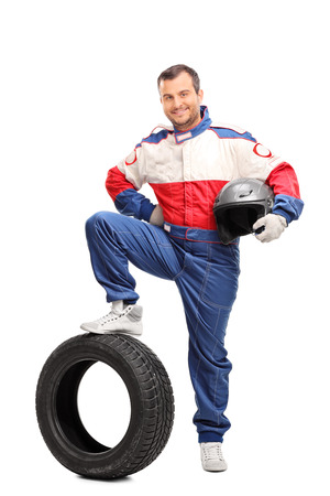 Full length portrait of a young male car racer holding a helmet and stepping on a tire isolated on white background