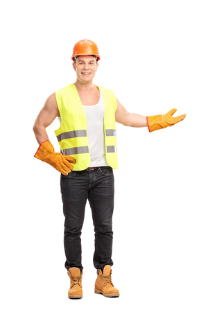 worker man: Full length portrait of a cheerful young construction worker gesturing with his hand and looking at the camera isolated on white background