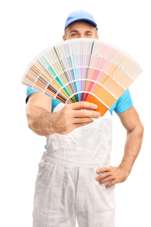 color swatch: Vertical shot of a young male house painter spreading a color swatch in front of his face isolated on white background with the focus on the swatch
