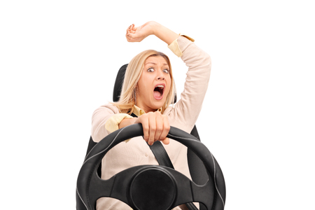 Studio shot of a terrified woman shot in the moment before a car crash isolated on white background