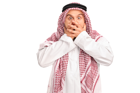 hand in mouth: Shocked male Arab covering his mouth with his hands and looking at the camera isolated on white background