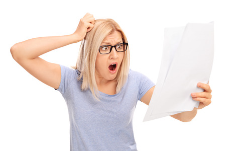 disbelief: Shocked blond woman looking at a piece of paper in disbelief isolated on white background Stock Photo