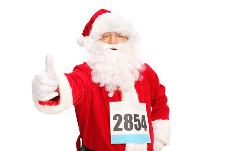 posing  agree: Santa Claus with a race number on his chest giving a thumb up and looking at the camera isolated on white background