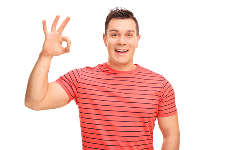 posing  agree: Joyful young man making an OK hand sign and looking at the camera isolated on white background