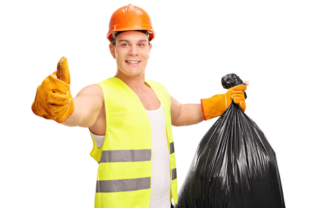 posing  agree: Young male waste collector holding a trash bag and giving a thumb up isolated on white background