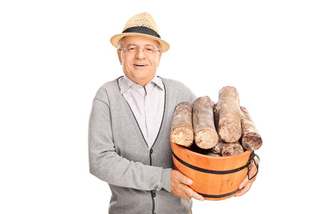 log basket: Cheerful senior gentleman carrying a pile of logs in a wooden basket isolated on white background