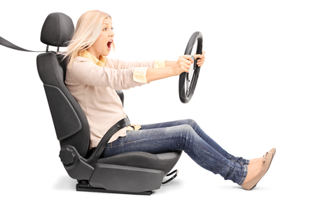 Young blond woman driving very fast seated on a car seat fastened with seatbelt isolated on white background 스톡 콘텐츠