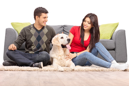 white dog: Young couple sitting with their dog in front of a gray sofa isolated on white background Stock Photo