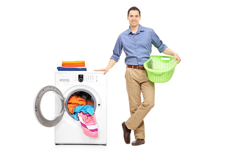 man laundry: Full length portrait of a cheerful young man holding an empty laundry basket and standing next to a washing machine full of clothes isolated on white background