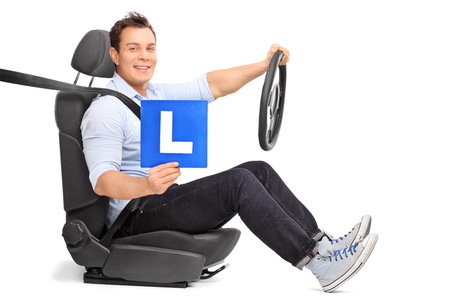 car isolated: Young man holding a steering wheel and an L-sign seated on a car seat isolated on white background