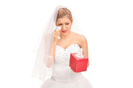 mujer sola: Novia joven en un vestido de novia llorando y secándose las lágrimas aisladas sobre fondo blanco Foto de archivo