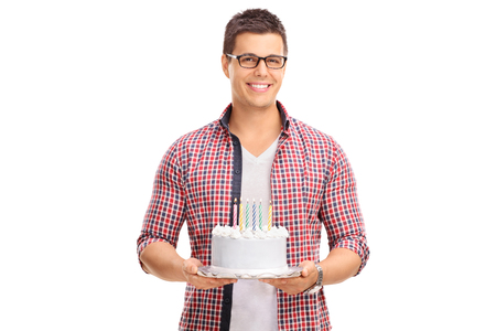 background person: Cheerful young guy holding a birthday cake and looking at the camera isolated on white background Stock Photo