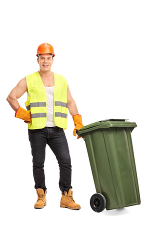Full length portrait of a young male waste collector posing next to a green trash can isolated on white background