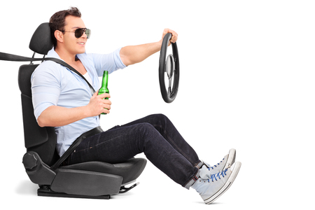 careless: Careless young man driving and holding a bottle of beer isolated on white background Stock Photo