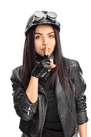 shush: Vertical shot of a female biker holding a finger on her lips and looking at the camera isolated on white background