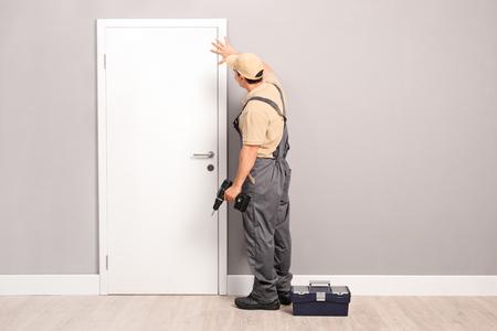 若い便利屋部屋で電動ハンドドリルと白いドアをインストールします。