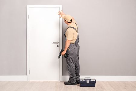Young handyman installing a white door with an electric hand drill in a room