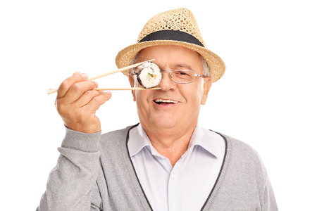childish: Joyful senior gentleman holding a piece of sushi in front of his eye and looking at the camera isolated on white background