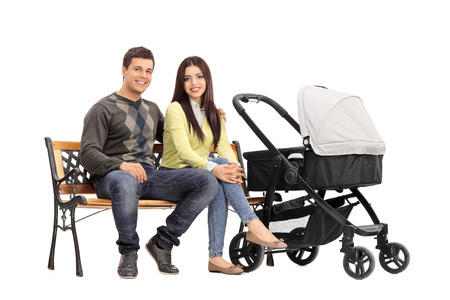 persona sentada: Los padres jóvenes sentados en un banco de madera con un cochecito de bebé a su lado aisladas sobre fondo blanco