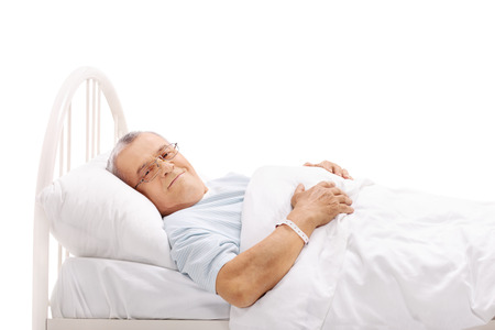 old man happy: Senior patient lying on a hospital bed and looking at the camera isolated on white background
