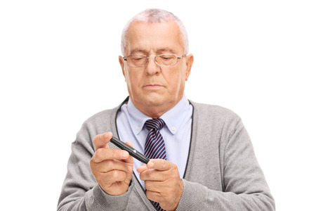 blood sugar level: Senior gentleman measuring his blood sugar level with glucometer isolated on white background