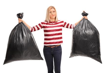 basura: Mujer joven Enfadado sosteniendo dos bolsas de basura negras y mirando a la cámara aislada en el fondo blanco