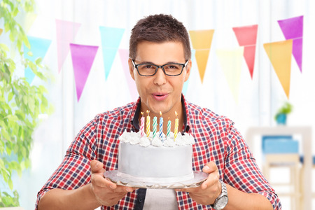birthday adult: Joyful young man blowing candles on a birthday cake and looking at the camera at home