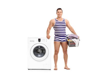 ropa interior: El hombre joven en una ropa interior de rayas sosteniendo un cesto de la ropa y de pie junto a una lavadora aislada en el fondo blanco