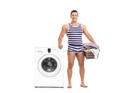 Young man in a striped underwear holding a laundry basket and standing next to a washing machine isolated on white background