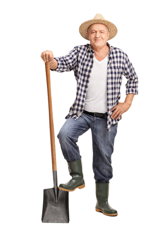 agricultural tools: Full length portrait of a mature farmer posing with a shovel isolated on white background Stock Photo