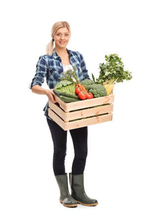 新鮮な有機野菜の完全な木枠を押し、白い背景で隔離のカメラ目線の女性農業労働者の完全な長さの肖像画
